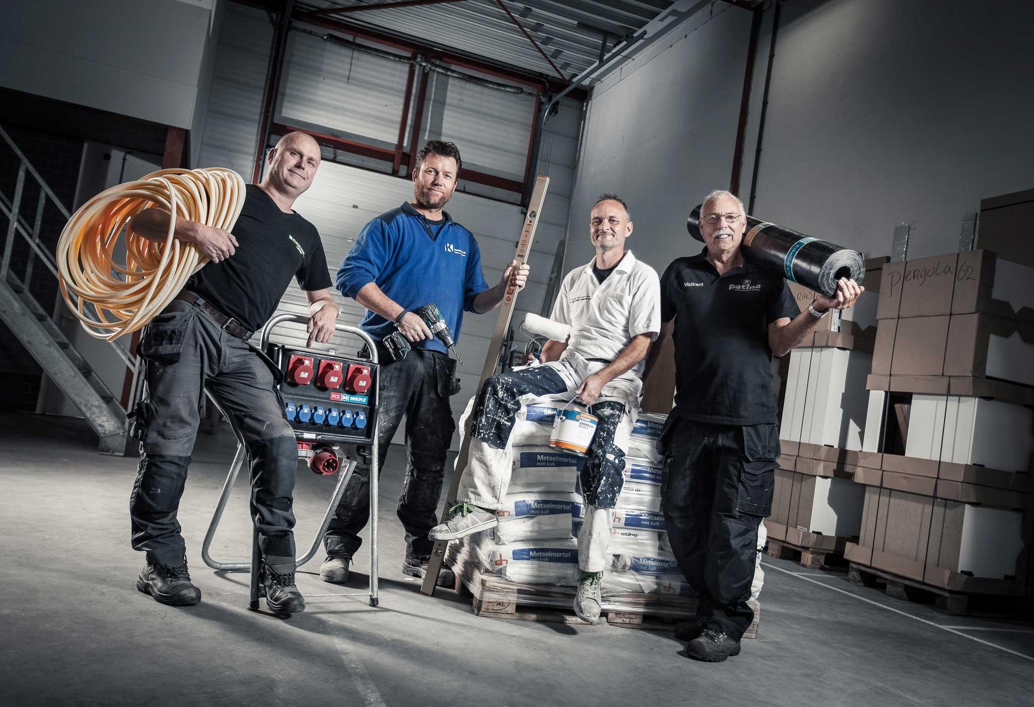 Vier mannen in een hal die klusproducten vasthouden